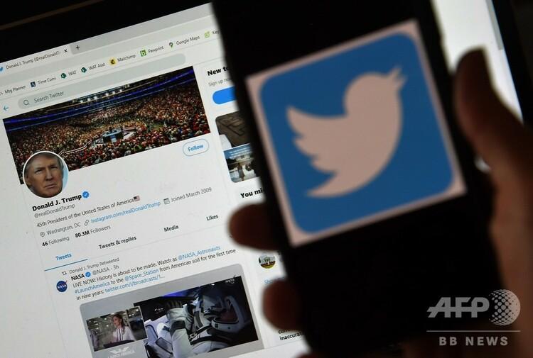 ドナルド・トランプ米大統領のツイッター投稿を背景に、携帯電話に表示されたツイッターのロゴ(2020年5月27日撮影)。(c)Olivier DOULIERY / AFP