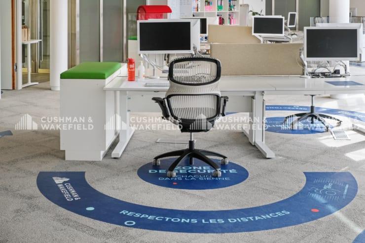 従業員は毎回使い捨てのデスク・シートを使用し、デスク使用後には消毒液で除菌する(フランス/C&W提供)