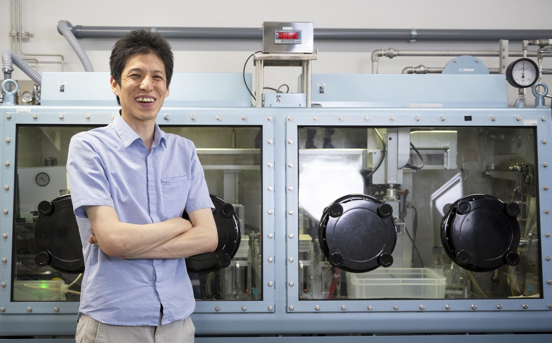 「ハイスループット電解液探索システム」の前に立つ国立研究開発法人 物質・材料研究機構(NIMS)の松田翔一氏 博士(工学)
