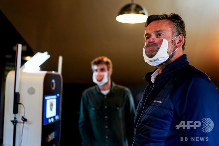 ベルギー・ブリュッセルで、口元が印刷されたマスクを着用する男性(2020年6月8日撮影)。(c)Kenzo TRIBOUILLARD / AFP