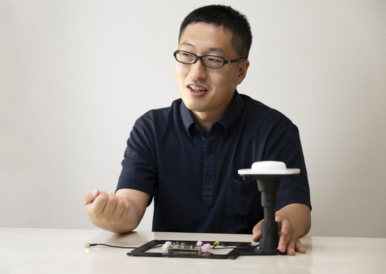 「海洋観測用ドローン」について説明する東京大学生産技術研究所海中観測実装工学研究センターの横田裕輔氏(握っているのは、実機にも搭載されているGNSSアンテナ)
