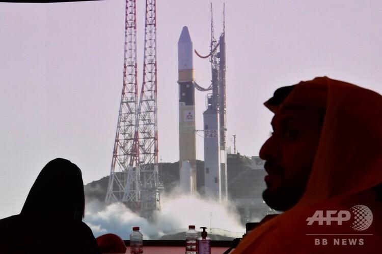 アラブ首長国連邦(UAE)ドバイにあるUAEの宇宙機関「ムハンマド・ビン・ラシード宇宙センター」で、日本で行われた火星探査機「ホープ」の打ち上げの様子を映し出すスクリーンを見る人たち(2020年7月19日撮影)。(c)Giuseppe CACACE / AFP