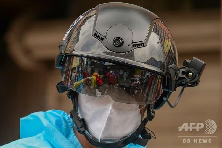 インド・ムンバイで、体温測定用サーモグラフィーが搭載されたスマートヘルメットと防護服を着用し住民の検温を行う非営利団体「バラティヤ・ジェン・サンガタナ」の医療ボランティア(2020年7月21日撮影)。(c)INDRANIL MUKHERJEE / AFP