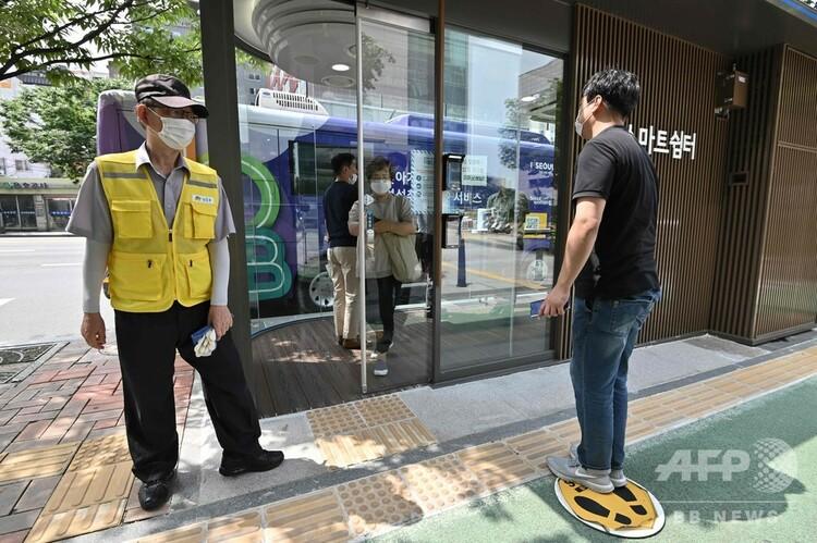 韓国・ソウルのバス停に設置された、新型コロナウイルス対策が盛り込まれたハイテク待合所に入るため検温を受ける男性(右、2020年8月12日撮影)。(c)Jung Yeon-je:AFP