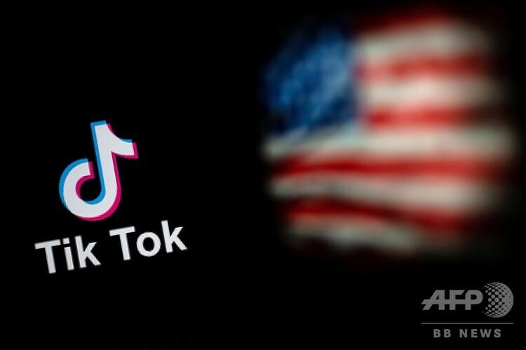 動画共有アプリ「ティックトック(TikTok)」のロゴ(左)と米国旗(右、2020年9月14日撮影)。(c)NICOLAS ASFOURI / AFP