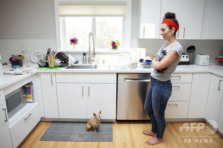 飼い犬と共に台所に立つコンサルタントの女性。在宅勤務のため、米サンフランシスコから約25キロ離れた別の町に転居した(2020年9月11日撮影)。(c)Brittany Hosea-Small / AFP
