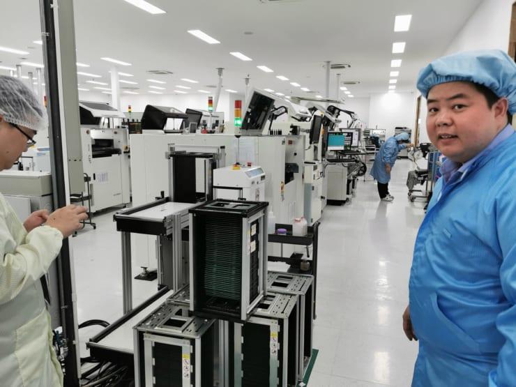 Gravitech ThailandのPCBA製造工場を案内するパン氏(右)。今Gravitech Thailandはバンコク近郊に5つの工場を展開している