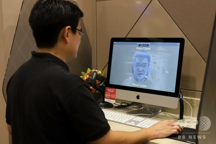 顔認証技術を使用して行政サービスへのアクセスを実演するシンガポール政府技術庁の職員(2020年10月1日撮影)。(c)MARTIN ABBUGAO / AFP
