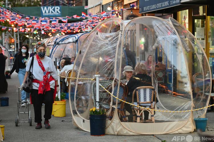 米ニューヨークのマンハッタンで、レストランの屋外に設置されたテントで食事をする人々(2020年10月15日撮影)。(c)Angela Weiss : AFP