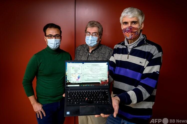 テキスト解析用のソフトウエアを使用するパソコンを手にして同僚らと並ぶ、スイスの新興企業「オルフアナリティクス」のクロード・アラン・ルートゥン最高経営責任者(中央、2021年1月6日撮影)。(c)Fabrice COFFRINI / AFP