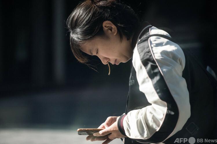 中国首都北京で、スマートフォンを使用する女性(2017年11月11日撮影、資料写真)。(c)FRED DUFOUR : AFP