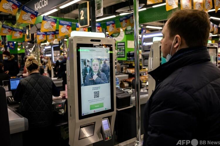 ロシアの首都モスクワにあるスーパー、ペレクリョストクのセルフレジで、顔認証決済を実演するX5リテール・グループの従業員(2021年3月9日撮影)。(c)Dimitar DILKOFF : AFP