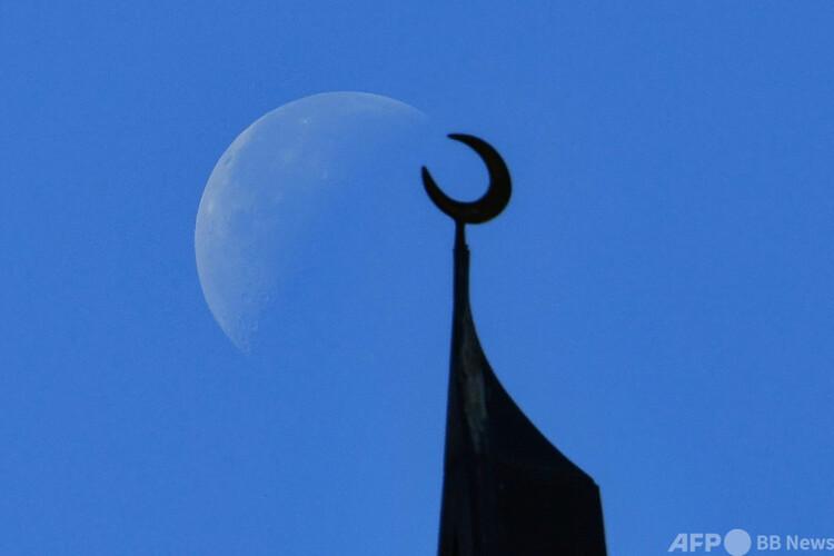 アラブ首長国連邦(UAE)ドバイのジュメイラビーチレジデンスの、三日月のシンボルが付いたモスクの屋根と、その向こうに見える月(2020 年1月18日撮影、資料写真)。(c)GIUSEPPE CACACE / AFP