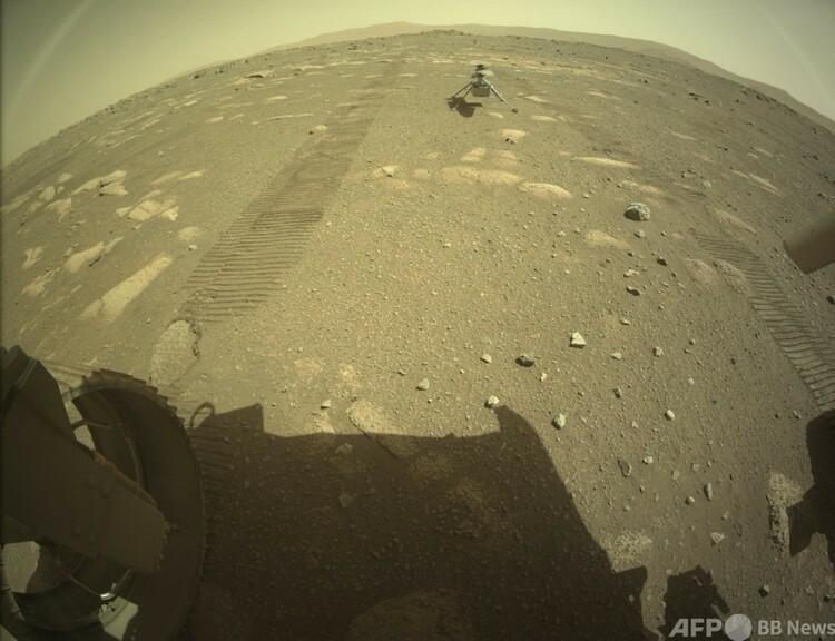 米航空宇宙局(NASA)の火星探査車「パーシビアランス」の後方に着地した小型ヘリコプター「インジェニュイティ」。NASA提供(2021年4月4日入手)。(c)AFP PHOTO / NASA/JPL-Caltech/HANDOUT