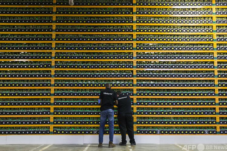 カナダ・ケベック州サンティアサントにあるビットコインのマイニング(採掘)企業、ビットファームズの施設で設備を点検する作業員ら(2018年3月19日撮影)。(c)Lars Hagberg / AFP