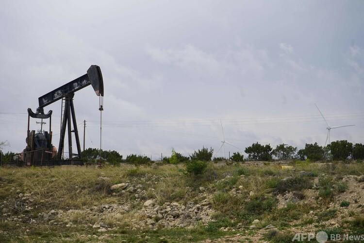 米テキサス州エルドラド近郊の風力タービンと、使われなくなった採油ポンプ(2021年4月16日撮影)。(c)Sergio FLORES : AFP