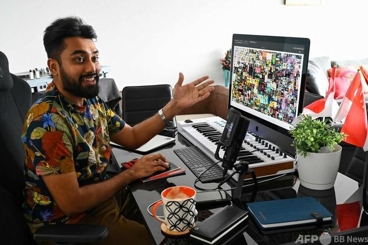 米国人アーティスト、ビープルのデジタルコラージュ作品(画面内)を非代替性トークン(NFT)として6930万ドル(約75億円)で落札したビグネシュ・スンダレサン氏(2021年4月7日撮影)。(c)Roslan RAHMAN / AFP
