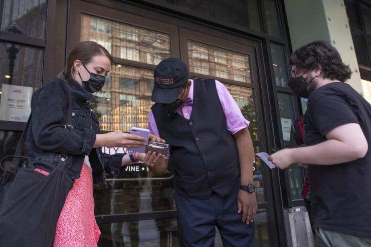 店の入り口でワクチン接種証明書を確認するスタッフ