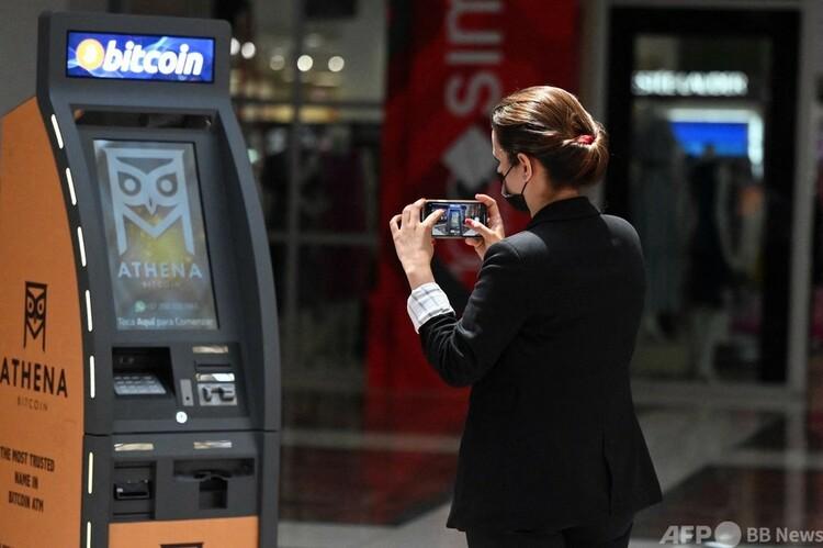 エルサルバドルの首都サンサルバドルに開設されたビットコインのATM(現金自動預払機)の写真を撮る女性(2021年6月24日撮影)。(c)MARVIN RECINOS : AFP