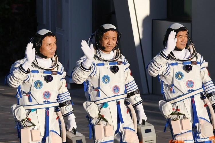 中国・酒泉衛星発射センターから打ち上げられる有人宇宙船「神舟12号」に乗り込む際の出発式で、手を振る3人の宇宙飛行士ら(2021年6月17日撮影)。(c)GREG BAKER : AFP
