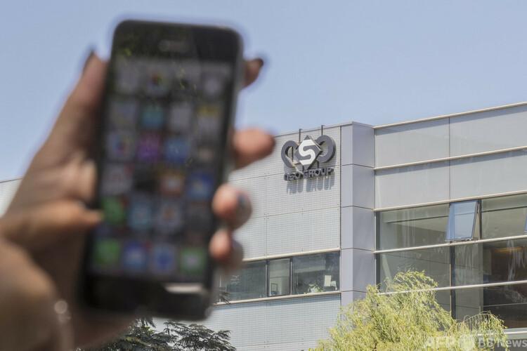 イスラエルのヘルツリヤにあるサイバー技術会社NSOグループが入居する建物前で、携帯電話を操作する女性(2016年8月28日撮影)。(c)JACK GUEZ : AFP