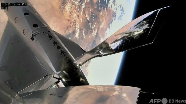 宇宙空間に達した宇宙旅行会社ヴァージン・ギャラクティックの宇宙船「スペースシップツー」の2号機「ユニティ」(左が機体の一部)から見た地球、米ニューメキシコ州一帯(2021年6月22日撮影)。(c)AFP PHOTO / Virgin Galactic