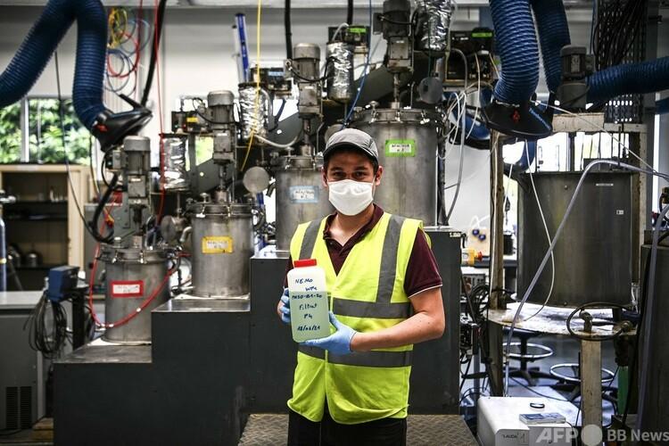 レアアースを含む溶液を手にした技術者。仏オルレアンのフランス地質調査所(BRGM)で(2021年6月22日撮影)。(c)Christophe ARCHAMBAULT : AFP