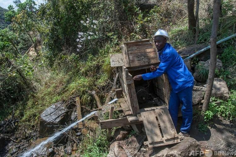 マラウイ北部のヨベヌコシで、水力発電装置を調整するコルレード・ヌコシさん(2021年8月23日撮影)。(c)AMOS GUMULIRA : AFP