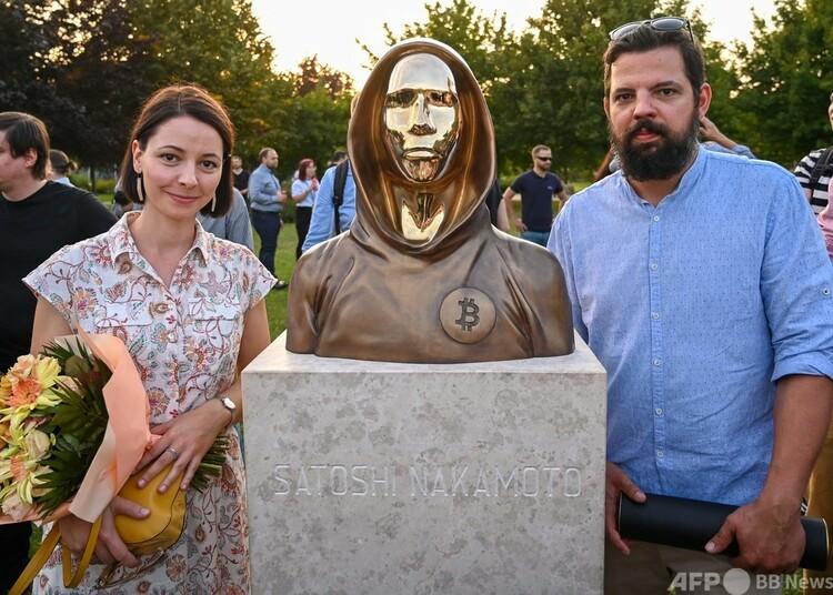 ハンガリー・ブダペストに登場した「サトシ・ナカモト」の像と制作者の2人(2021年9月16日撮影)。(c)ATTILA KISBENEDEK : AFP
