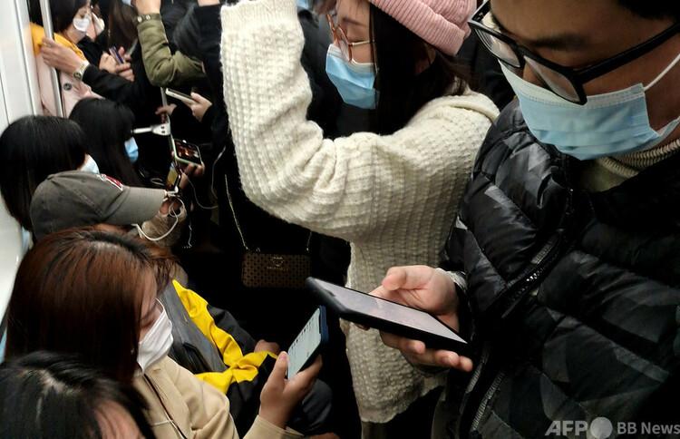 上海市の地下鉄でスマホを見る乗客たち(2020年12月3日撮影、資料写真)。(c)CNS:厳大明